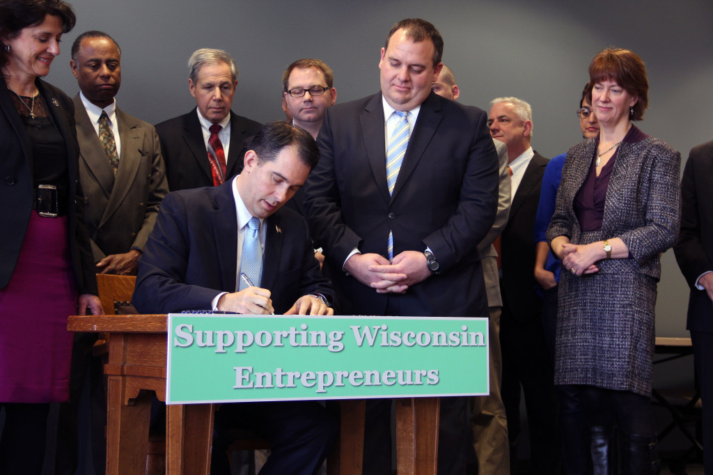 Wisconsin Gov. Scott Walker signs Assembly Bill 350, his state's crowdfunding bill, on Nov. 7, 2013 at University Research Park in Madison, Wis. | Photo by Allen Wagner